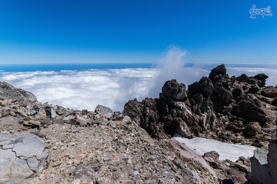 Les nuages s'écrasent sur les rochers au sommet comme des vagues contre des falaises