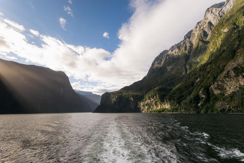 Les rayons matinaux du soleil percent les nuages et rasent les sommets de Milford Sound