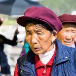 Une Ancienne En Pleine Prière Autour Du Rouleau Du Temple De Shangri-La. Les Tibétaines Ici Portent Une Casquette Violette.