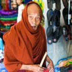 Un vieux moine au regard totalement égaré alors qu'il tente d'acheter des chaussettes