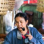 Une vendeuse du marché fumant la pipe