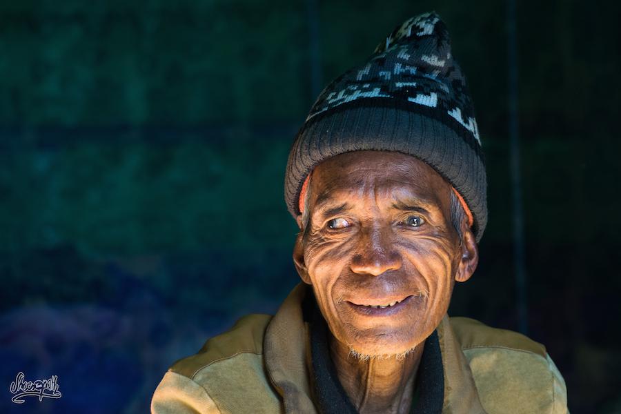 Un ancien de Mindat assis sur le pas de son logis