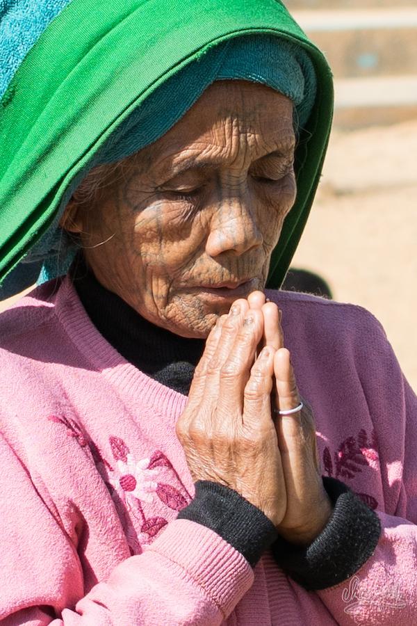 Brève prière en passant devant une statue de Jésus sur la place de l'église.
