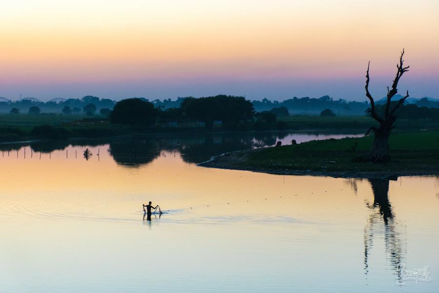 Un pêcheur remonte son filet pour la dernière fois de la journée, au crépuscule, près du pont d'U Bein