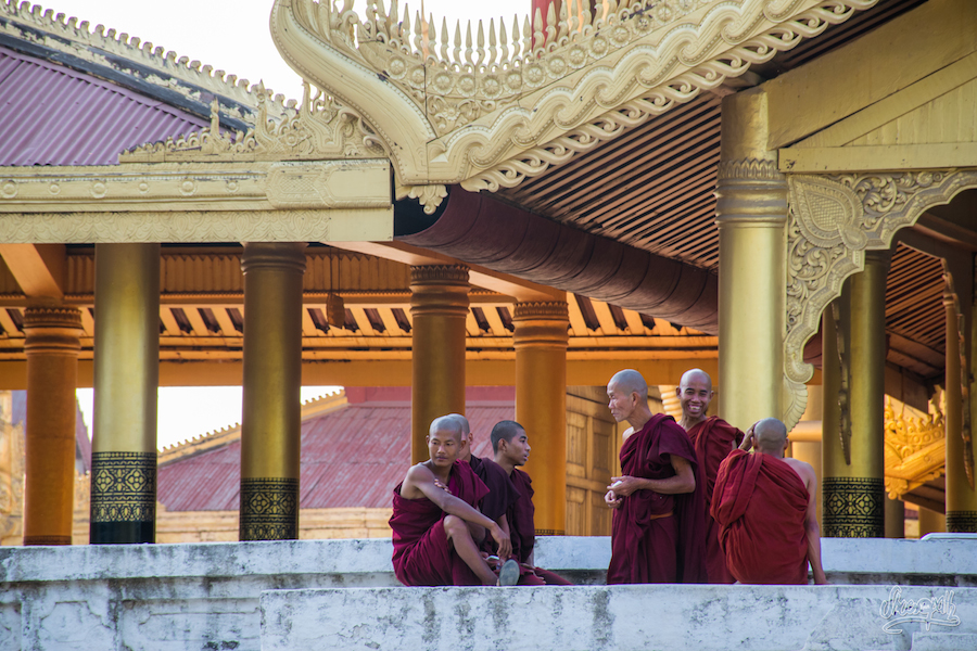 Groupe de moines devant les piliers dorés du palais royal de Mandalay