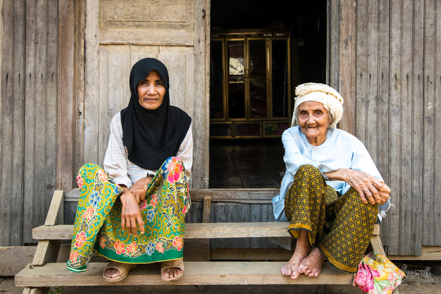 Cham mother and daughter on the door step of their house, just on the banks of the Mekong