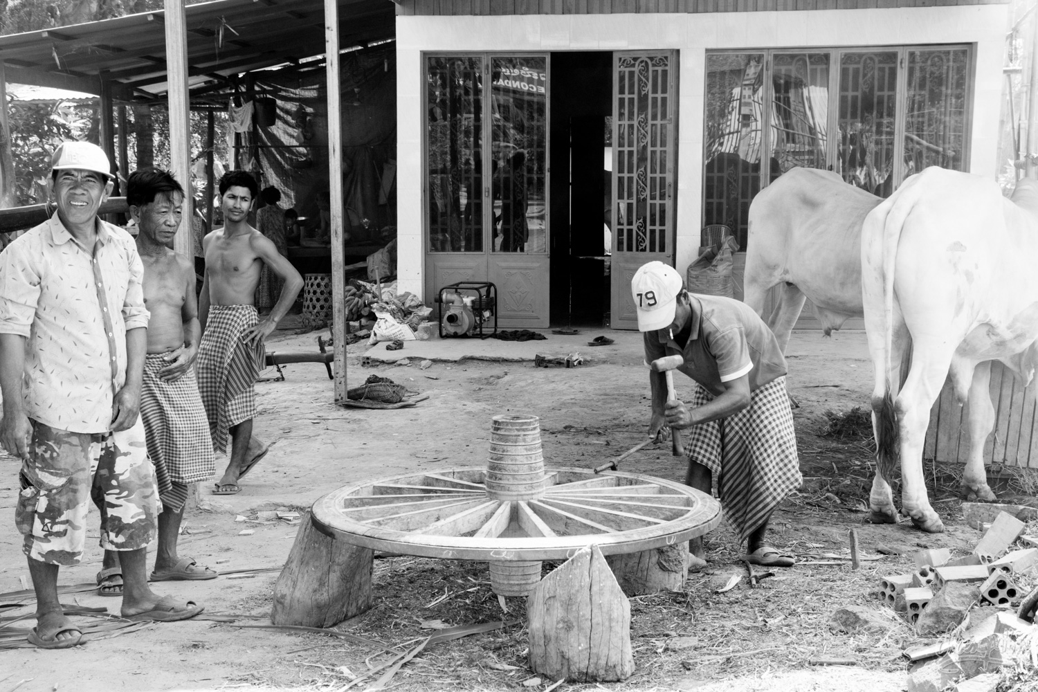 Reparing a oxcart wheel, a classic scene of the life along the Mekong in Cambodia