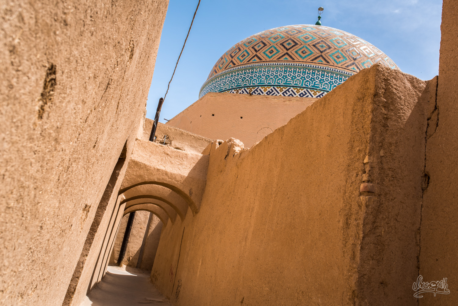 In the streets of Yazd old town center : mud walls and blue cupolas