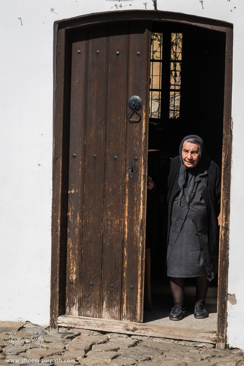 Une Vieille Dame Veille Sur L'église De Kakopetria, Tandis Que Quelques Touristes La Visite