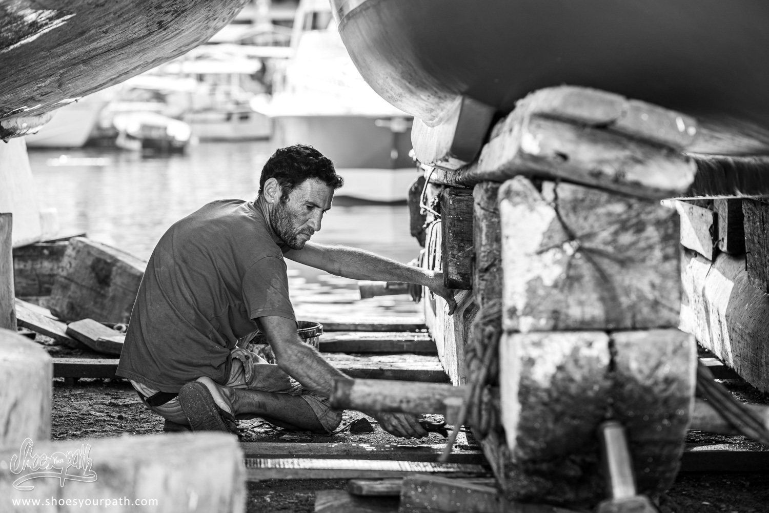A painter working on a boat in the Kyrenia harbor