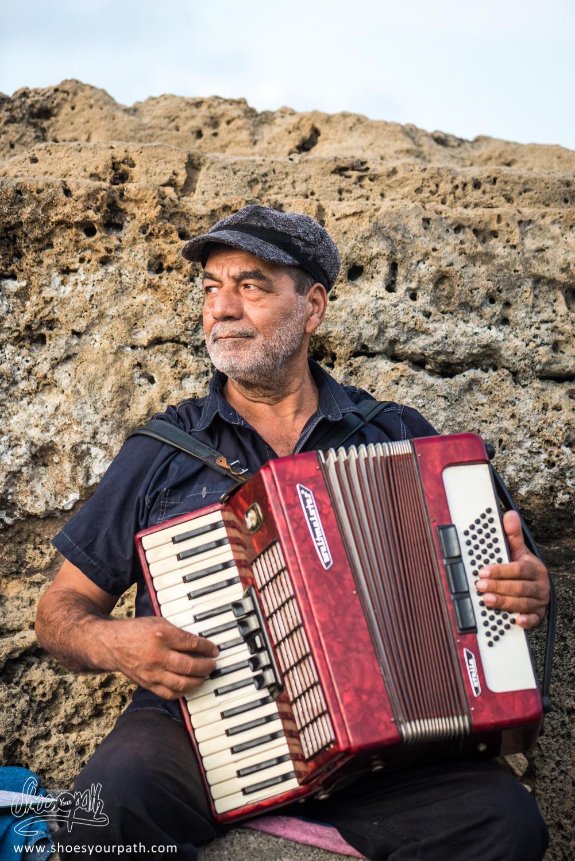Sur la jetée de Kyrenia, un homme joue de l'accordéon pour les passants